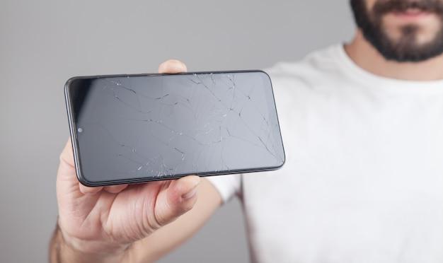 Człowiek posiadający czarny uszkodzony smartfon. zepsuty ekran