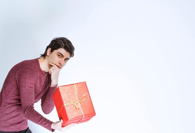 Człowiek posiadający duże czerwone pudełko.
