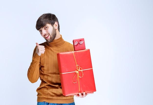 Człowiek posiadający duże i małe czerwone pudełka i ciesząc się nim.