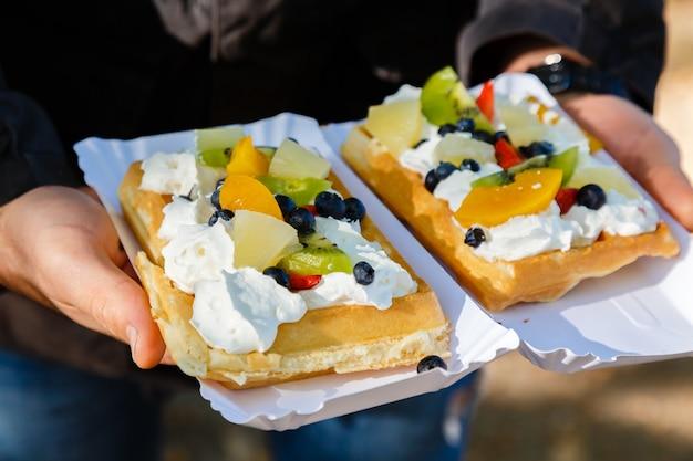 Człowiek posiadający dwa świeże ciasta gofrowe z owocami i bitą śmietaną na wakacje.
