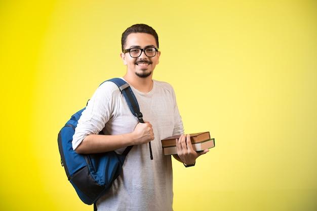 Człowiek posiadający dwie książki, patrząc prosto i uśmiechnięty.