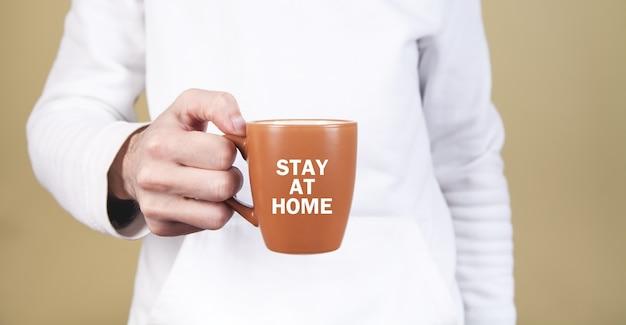 Człowiek posiadający filiżankę herbaty. zostań w domu