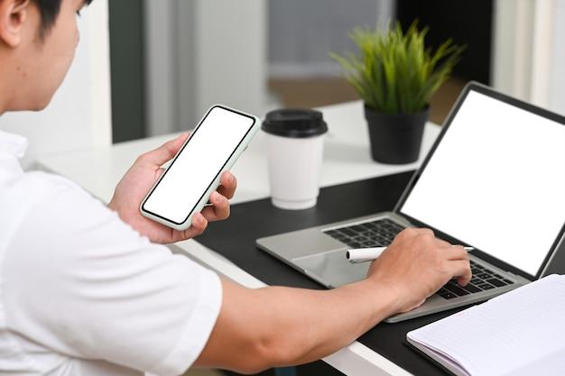 Człowiek posiadający inteligentny telefon i pracy z laptopem w nowoczesnym miejscu pracy.