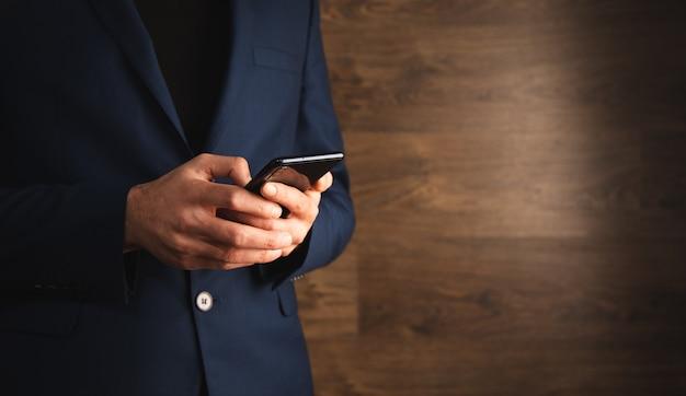 Człowiek posiadający inteligentny telefon na podłoże drewniane