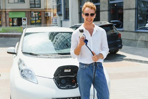 Człowiek posiadający kabel zasilający do samochodu elektrycznego w odkrytym parkingu. i zamierza podłączyć samochód do stacji ładującej na parkingu w pobliżu centrum handlowego