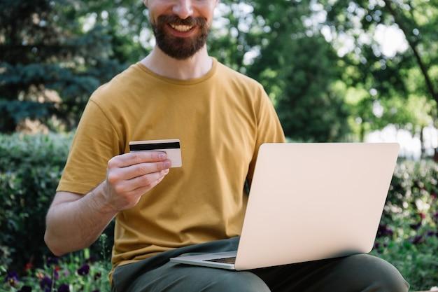 Człowiek posiadający kartę kredytową za pomocą laptopa, zakupy online. freelancer otrzymuje zapłatę