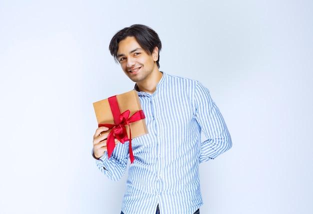 Człowiek posiadający kartonowe pudełko z czerwoną wstążką i pozytywne samopoczucie. zdjęcie wysokiej jakości