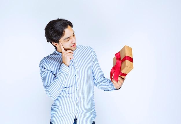 Człowiek posiadający kartonowe pudełko z czerwoną wstążką i wahania lub zakłopotany. zdjęcie wysokiej jakości