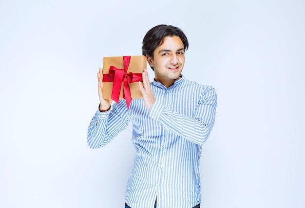 Człowiek posiadający kartonowe pudełko z czerwoną wstążką. zdjęcie wysokiej jakości