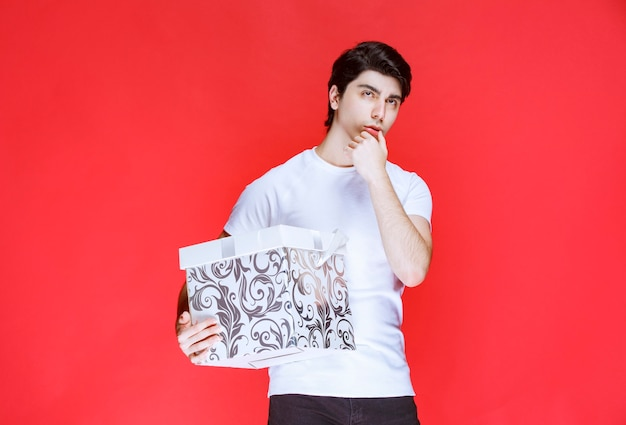 Człowiek posiadający kolorowe pudełko i myślenia.