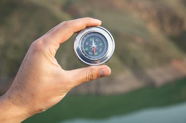 Człowiek posiadający kompas na powierzchni przyrody