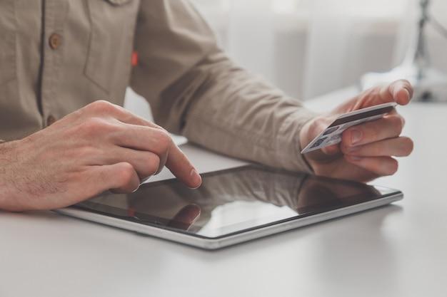 Człowiek posiadający komputer typu tablet i kartę kredytową przy stole, zakupy online.