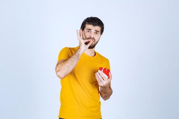 Człowiek posiadający kubek kawy i cieszący się smakiem.