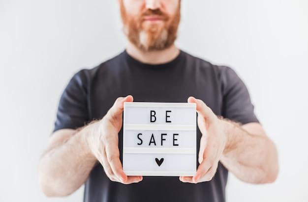 Człowiek posiadający lightbox z tekstem bądź bezpieczny