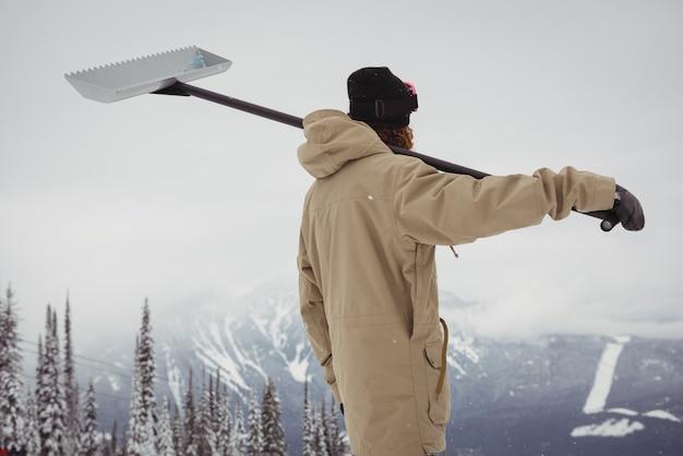Człowiek posiadający łopatę do śniegu w ośrodku narciarskim