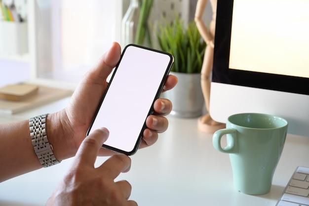 Człowiek posiadający makieta urządzenie mobilne inteligentny telefon w miejscu pracy biura