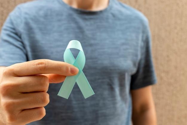 Człowiek posiadający niebieską wstążkę. zdrowie mężczyzn. niebieski listopad. miesiąc profilaktyki raka prostaty.