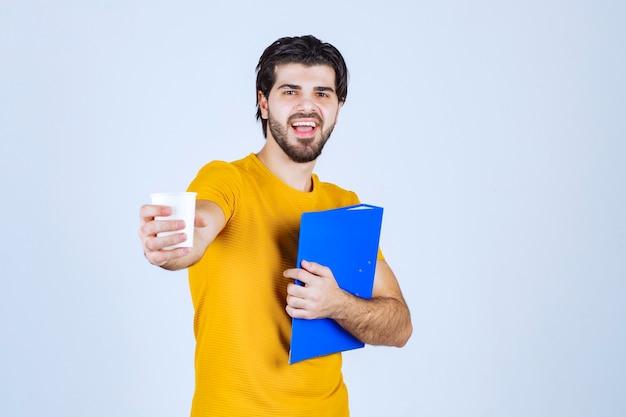 Człowiek posiadający niebieski folder i filiżankę kawy.