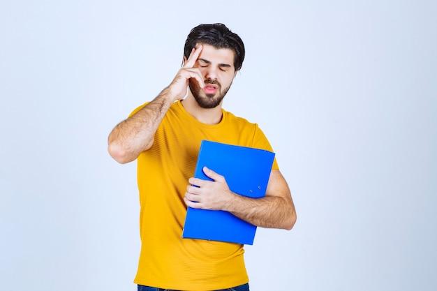 Człowiek posiadający niebieski folder i myślenia.
