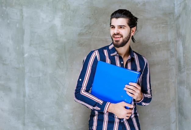 Człowiek posiadający niebieski folder raportu i uśmiechnięty.