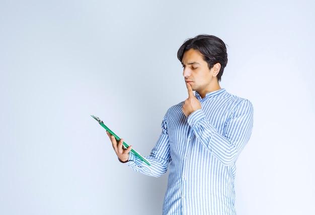 Człowiek posiadający niebieski i zielony foldery raportu i sprawdzanie ich. zdjęcie wysokiej jakości