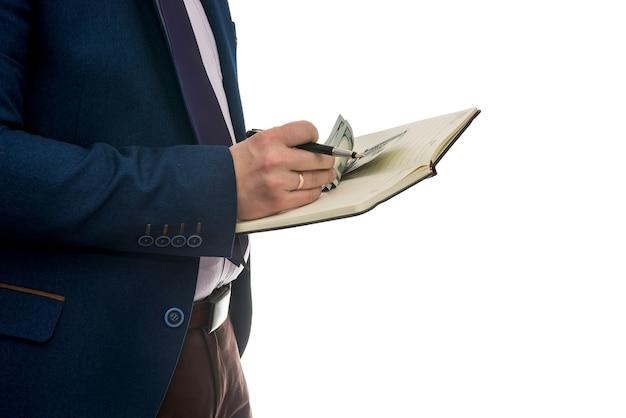 Człowiek posiadający otwarty notatnik podpisuje umowę kupna lub dzierżawy z gotówką na białym tle.