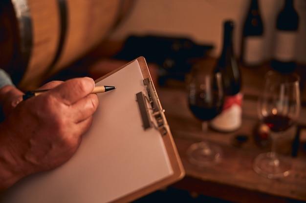 Człowiek posiadający schowka i dotykając kartki papieru piórem. kieliszki i butelki czerwonego wina w tle