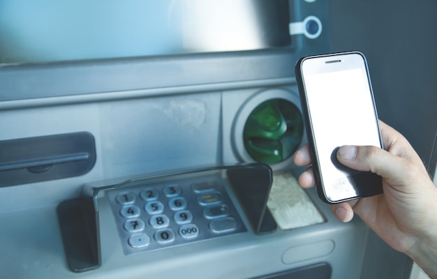 Człowiek posiadający smartfon. bankomat. transakcja online. koncepcja bankowości