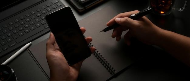 Człowiek posiadający smartfon i robienie notatek
