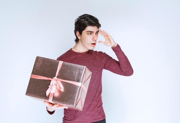 Człowiek posiadający srebrne różowe pudełko i myślenia.