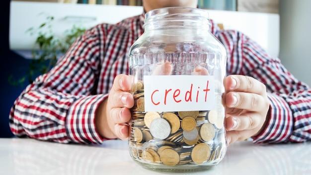 Człowiek posiadający szklany słoik z monetami z jego oszczędności. pojęcie finansów, wzrostu gospodarczego i oszczędności bankowych.