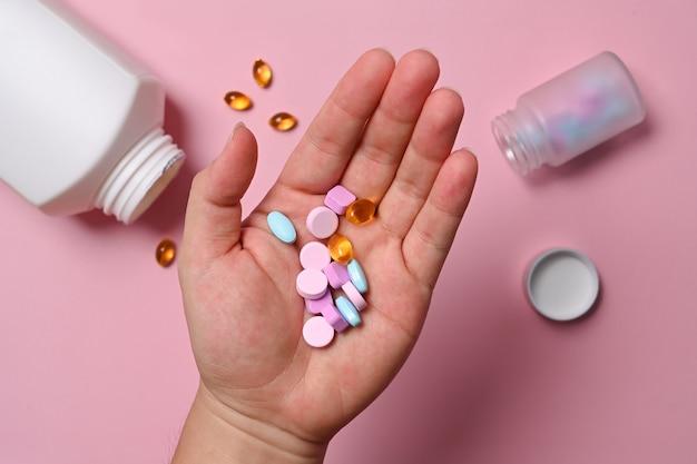 Człowiek posiadający tabletki medyczne i witaminy na różowym tle.