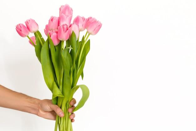 Człowiek posiadający tulipany. szablon karty podarunkowej, plakatu lub karty z pozdrowieniami - mężczyzna trzyma bukiet tulipanów dla kobiety. dzień matki, walentynki, koncepcja dzień kobiet. 8 marca prezent