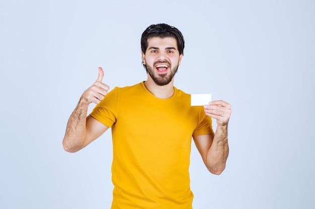 Człowiek Posiadający Wizytówkę I Pokazując Kciuk Do Góry. Darmowe Zdjęcia