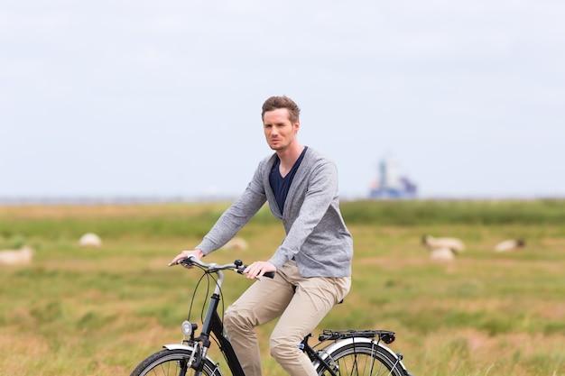 Człowiek posiadający wycieczkę rowerową z rowerem przy grobli z owcami