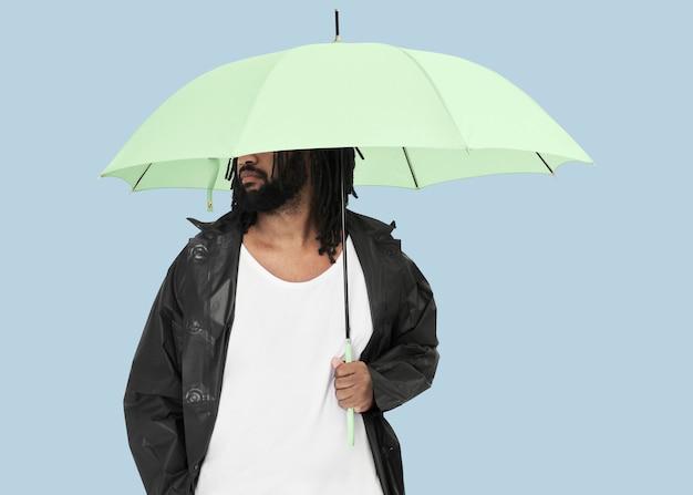Człowiek posiadający zielony parasol