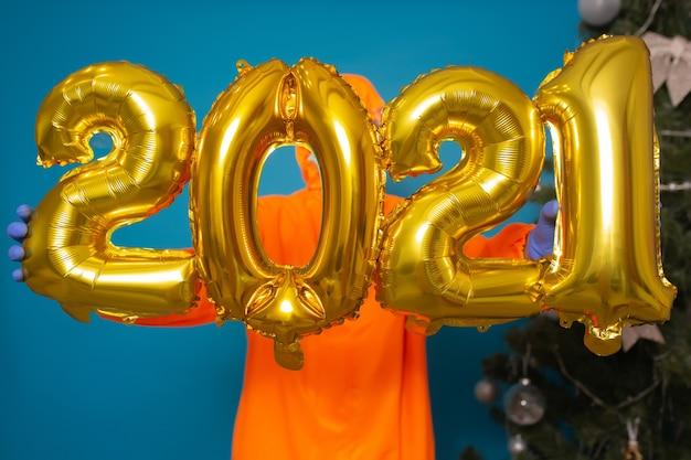 Człowiek posiadający złote balony z numerami 2021