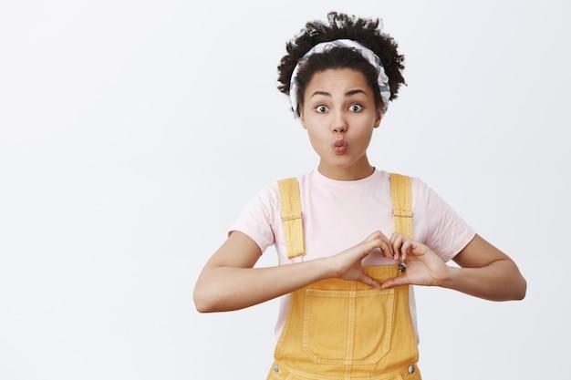 Człowiek potrzebuje miłości. portret pełnego nadziei, uroczego i delikatnego afroamerykanina w żółtym kombinezonie i opasce, pokazujący gest serca w pobliżu klatki piersiowej i składane usta w pocałunku, pozujący na szarej ścianie