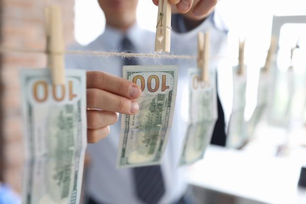 Człowiek powiesić sto dolarów z clothespin na linie