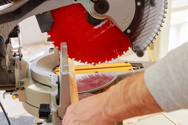 Człowiek, pracownik piłowanie drewna piłą tarczową, maszyna do cięcia. produkcja mebli. akcesoria. mdf, płyta wiórowa.