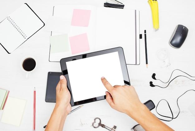 Człowiek pracujący na komputerze typu tablet z pustego ekranu notatnika i inteligentnego telefonu na białym stole