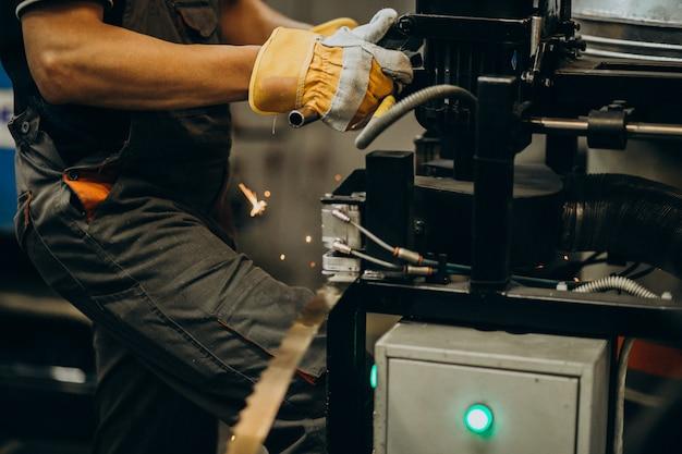 Człowiek pracujący nad stalową fabryką i sprzętem do produkcji stali
