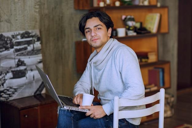 Człowiek pracujący w domowym biurze przy filiżance kawy. zdjęcie wysokiej jakości