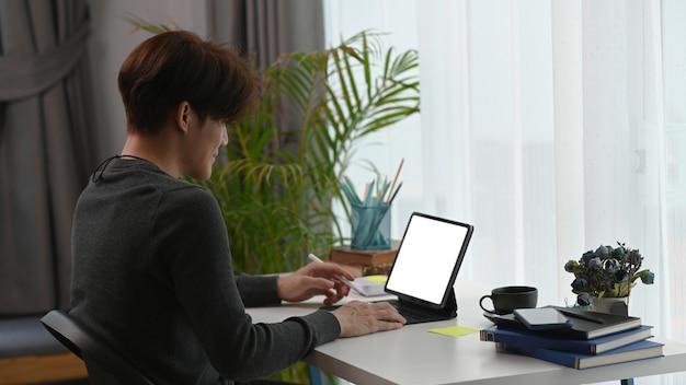 Człowiek pracujący w domu z pustym ekranem cyfrowy tablet w miejscu pracy.