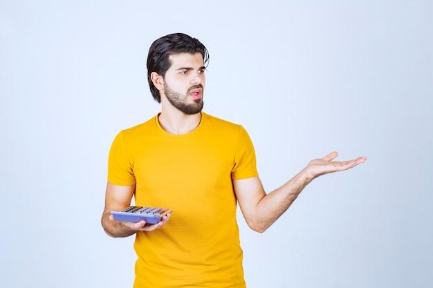 Człowiek pracujący z kalkulatorem i wygląda na niezadowolony.