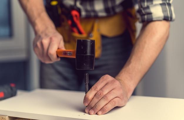 Człowiek pracujący z młotkiem i bit do otworu podczas procesu produkcji mebli drewnianych