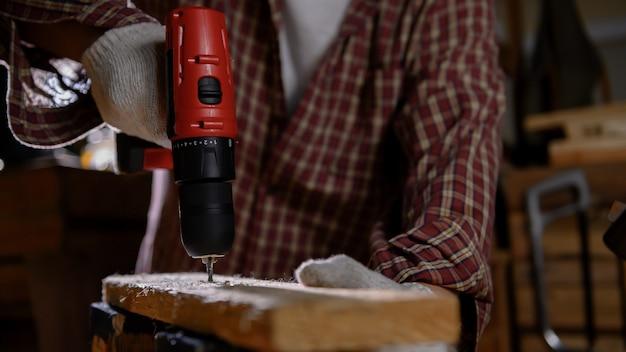 Człowiek pracuje w godzinach nadliczbowych w nocy. obróbka drewna i diy vintage drewniane do dekoracji wnętrz. warsztat stolarski i rzemieślniczy.