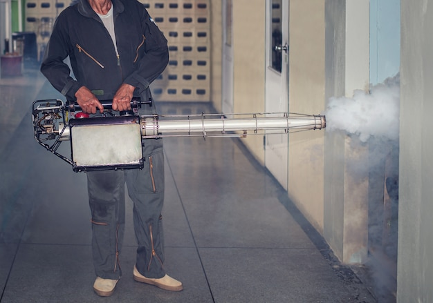 Człowiek pracuje w mgle rozpylającej, pozbyć się komarów, aby powstrzymać rozprzestrzenianie się gorączki denga