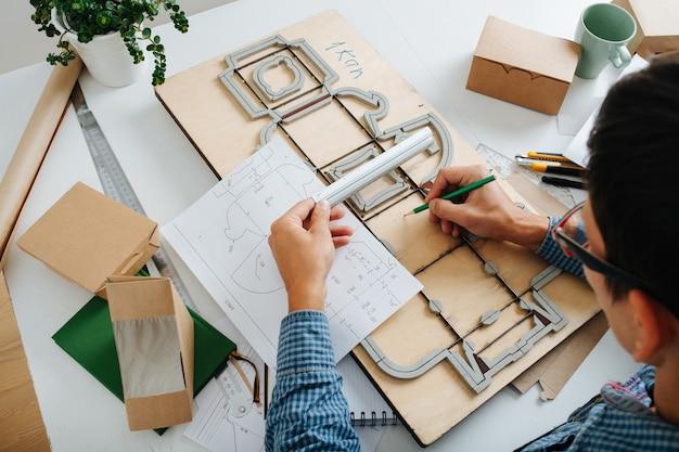 Człowiek pracuje z gotowymi pudełkami rysunkowymi i płytą wykrawającą