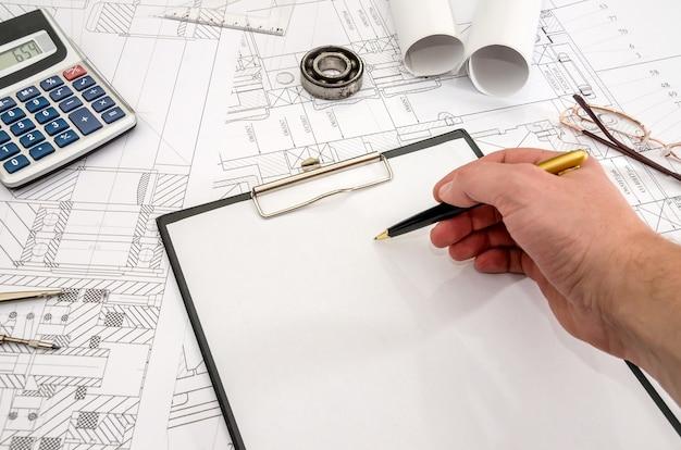 Człowiek pracuje z rysunkiem technicznym, częściami maszyn.